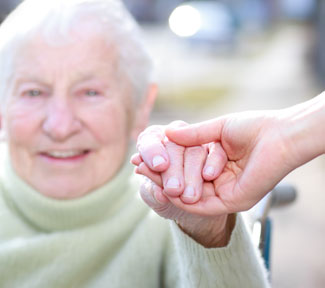 A volunteer holding an elderly woman's hand