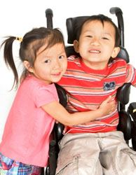 photo of children hugging.  One is in a wheelchair.