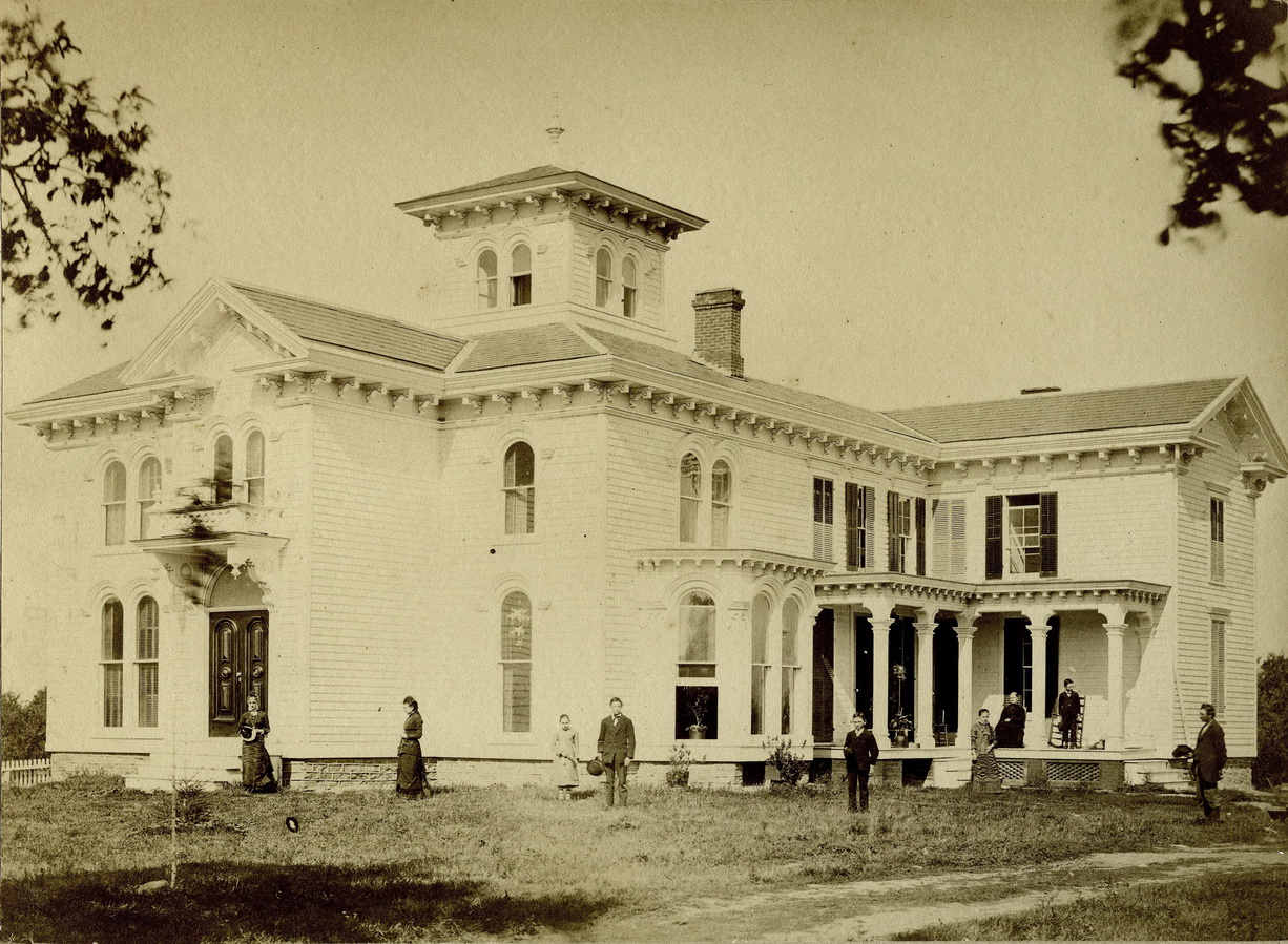 Image of large house with fancy eave trim and cupola and family members standing in yard