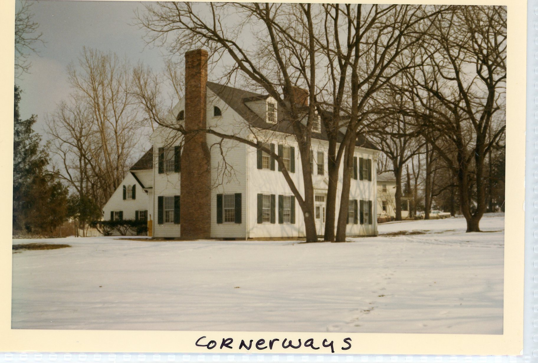 Image of white clapboard home, called Cornerways, with green shutters